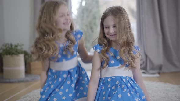 Thumbnail for Cheerful Caucasian Little Girl Looking at Twin Sister and Caressing Her Hair. Smiling Children in