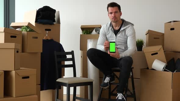 Thumbnail for A Moving Man Sits on a Chair in an Empty Apartment and Shows a Smartphone with a Green Screen