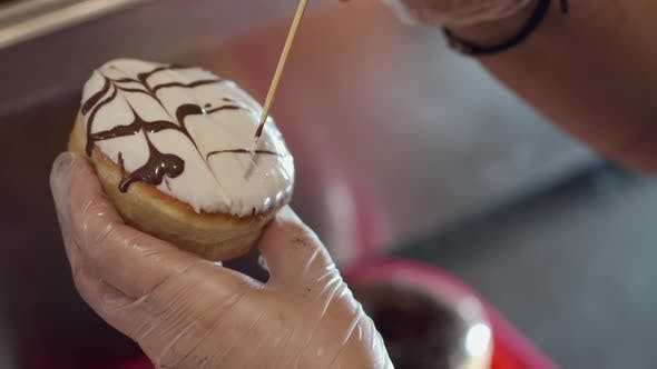 The Baker Is Decorating a Donut with a Topping