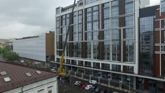 Thumbnail for Aerial View of Street with Crane Lifting Glass Panels on the Building Top