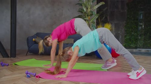 Mom and Daughter Doing Downward Facing Dog Indoors