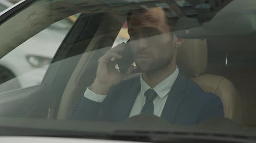 Businessman Talking on Phone in Front Car Seat