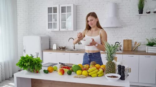 Young woman in the kitchen. Beautiful girl standing near the table with organic food.