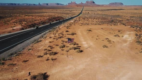Thumbnail for Drone Camera Tilts Up To Reveal American Flag Waving in the Middle of Monument Valley, Bikers