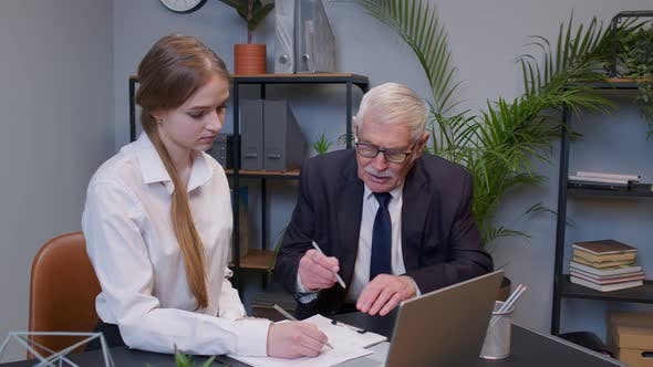 Senior Businessman Company Entrepreneur Ceo Examining Financial Data with Young Woman Secretary
