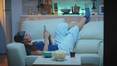 Woman Lying on Sofa Checking Cell Phone