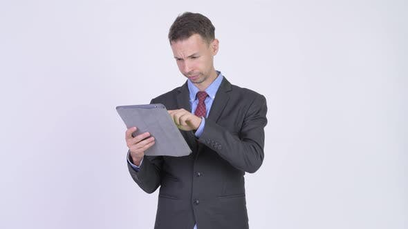 Thumbnail for Studio Shot of Happy Businessman Using Digital Tablet and Getting Good News