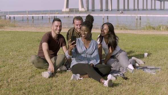 Thumbnail for Smiling Friends Looking at Smartphone While Posing for Selfie