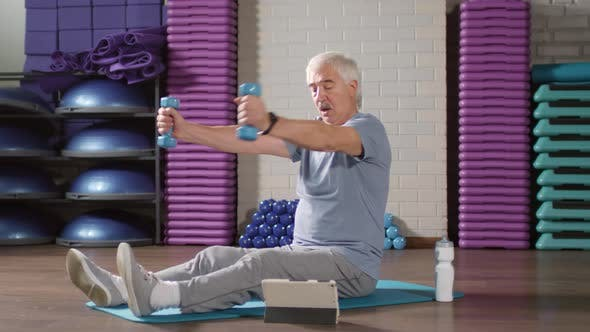 Thumbnail for Retired Man Exercising According to Video Lesson