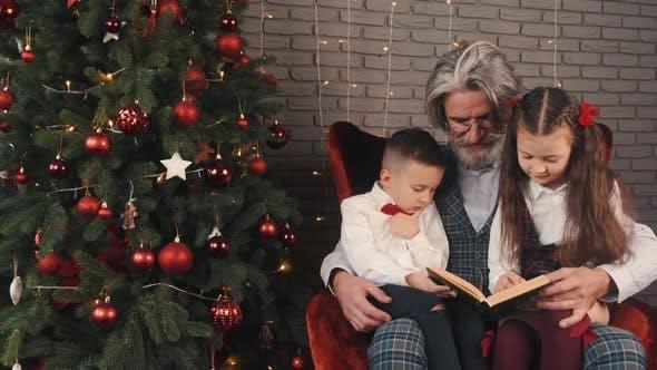 Thumbnail for Großvater und Kinder lesen ein Buch an Heiligabend