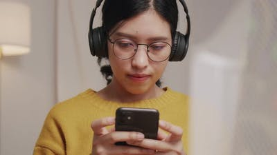 Young woman typing message on mobile and listening to music.