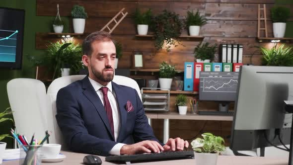 Thumbnail for Zoom in Footage of Handsome Guy in Suit Working Alone in the Office