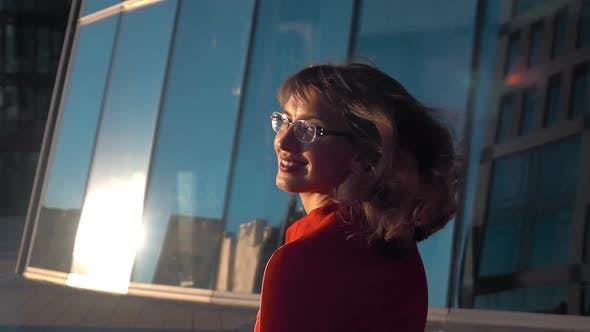 Thumbnail for Beautiful Girl Goes on an Office Building, She Turns Around and Looks Very Happy and Fun. Slow