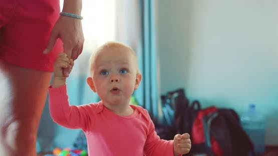 Little Child Walks with the Mother at the Apartment By the Hand