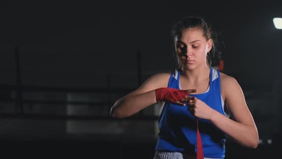 Cover Image for Woman Fighter Preparing for Battle Winds Up Hands in Boxing Bandages