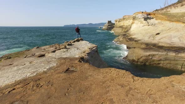 Cover Image for Aerial shot of backpacker standing on rock overlooking Pacific Ocean