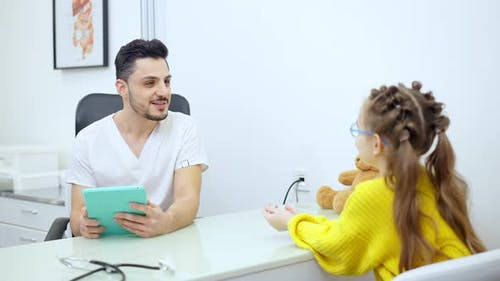 Positive Pediatrician Talking with Little Patient Holding Tablet