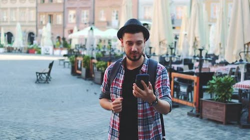 Tourist Making Video Call on Smartphone and Showing His Place of Visit