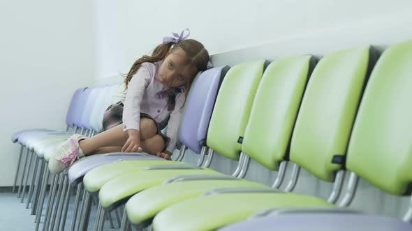 Thumbnail for Sad Little Girl Sitting Alone in a Chair and Sad. Depression in Young Children at School. The Girl
