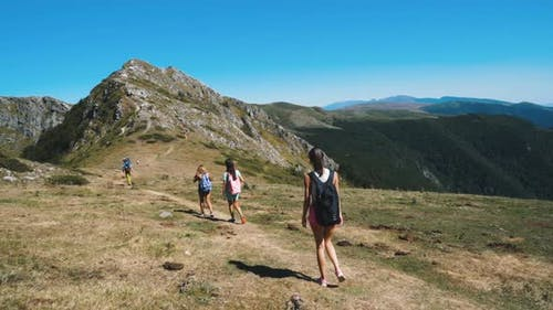 Group of Young Hikers with Backpacks Hiking on Rocky Mountain Hills with Beautiful View