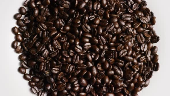 Rotating shot of delicious, roasted coffee beans on a white surface - COFFEE BEANS