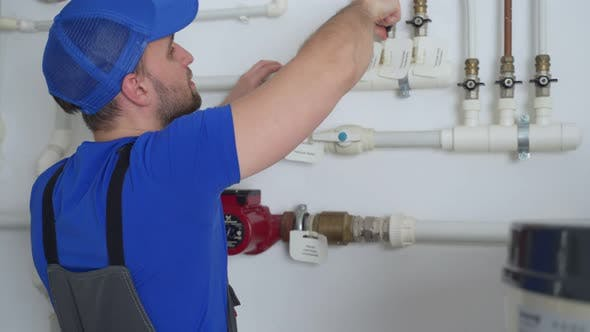 Uniformed Plumber is at Work  Closing and Opening the Taps