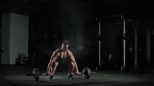 Weightlifting Kaukasischer Athletischer Mann führt Übungen mit Langhantelhebungen Langhantel durch und nimmt Gewichte