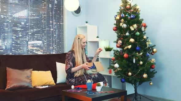 Thumbnail for Pretty Girl Hangs Toys on Christmas Tree with Skyscrapers on the Background