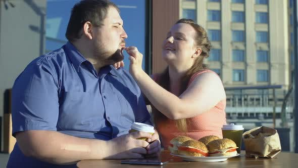 Thumbnail for Smiling Woman Treating Boyfriend French Fries, Fat Couple Date, Unhealthy Food