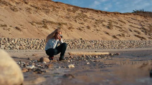 Photographer Crouching And Using Slr Camera