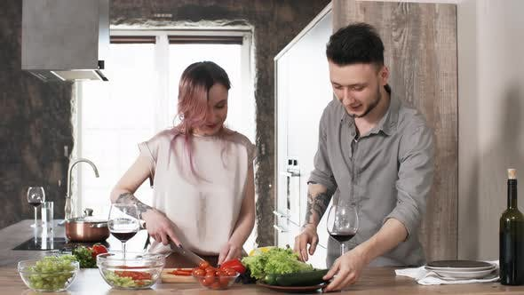 Thumbnail for Young Cheerful Couple Making Salad and Drinking Wine