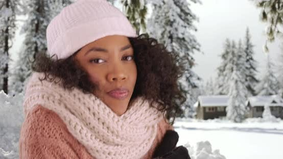 Thumbnail for Close up of cute black female in cozy hat and sweater shivering in snowy forest