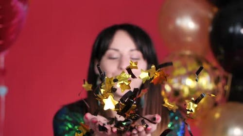 Happy Woman Blowing Gleaming Confetti To Camera