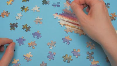 A Group of Puzzles, Hands on Blue Table Background. Puzzle Game, Preschool Education. Puzzle Pieces