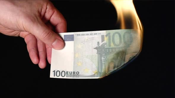 Thumbnail for A human hand holds one hundred euro flaming on a black background