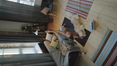 Woman Having Yoga Practice at Home with Dog