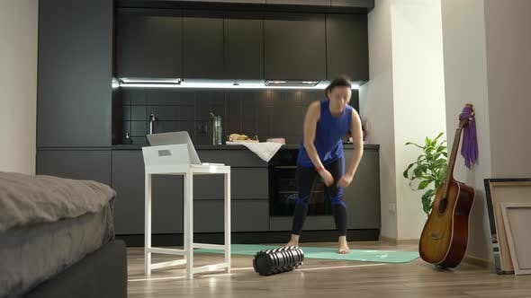 Thumbnail for Girl in workout sportswear doing online fitness exercises in kitchen at home during quarantine