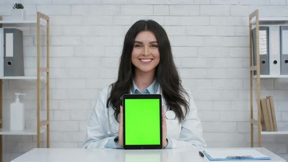 Female Doctor Showing Digital Tablet With Green Screen In Clinic
