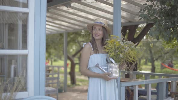 Thumbnail for Cute Young Woman in Straw Hat and White Dress Smiling While Sniffing Wild Flowers in a Watering Can