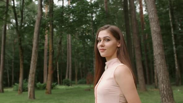 Thumbnail for Portrait of Girl Model. Woman in Good Mood Standing in Park, Looking Into Camera Smiling Trees