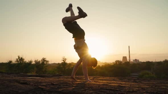 Stylish man dancing break dance against the backdrop of a beautiful sunset. Slow motion