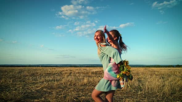 Cover Image for Mom and Daughter Walk, Have Fun and Fool Around in a Dry Grass Field