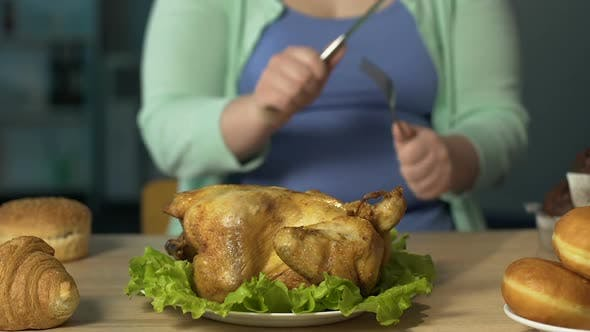 Thumbnail for Plump Lady Sharpening Knife Against Fork, Getting Ready to Eat Big Roast Chicken
