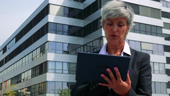 Thumbnail for Business Middle Age Woman Works on the Tablet - Company Building in the Background
