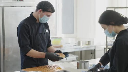 Concentrated Man Cutting Off Crust From Baked Cake Dough As Blurred Woman Packing Muffins for