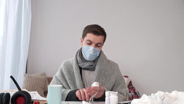 Thumbnail for Sick Man in Mask and Wrapped in Blanket Check Blood Oxygen at Home