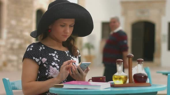 Thumbnail for Beautiful Girl Sitting in Street Cafe, Typing Message, Chatting on Smartphone