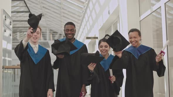 Cheerful Graduates Tossing Hats Up