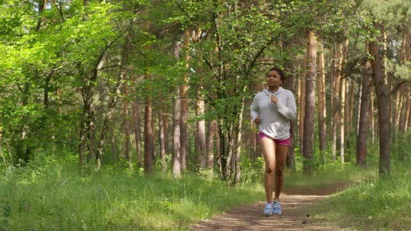 Thumbnail for Athletic Black Girl Running Alone in Summer Forest