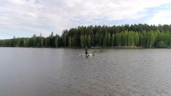 Thumbnail for Aerial view of lake surrounded by a forest with fishermens